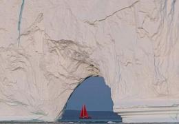 Крошечная лодка проплывает возле огромного айсберга