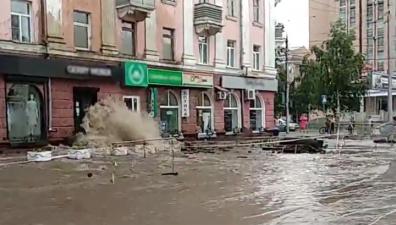 Поток воды из прорванной трубы разбил стекла в магазинах и затопил улицу. Видео