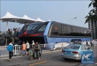 Китайский автобус, который проезжает над автомобилями